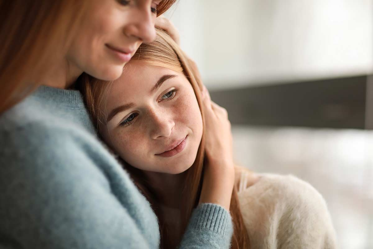 Mother embracing daughter explaining what are trauma triggers